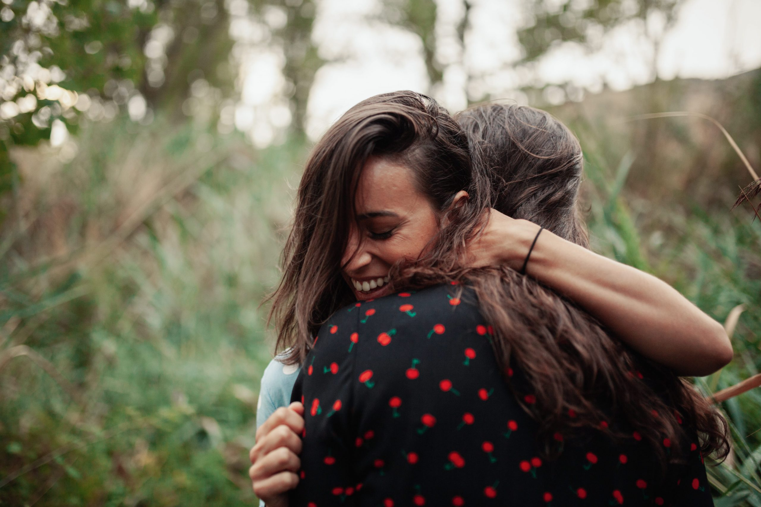 A young woman warmly embraces her friend.